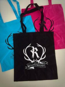 Turquoise, pink and black tote bags with Rovaniemi roller derby logo