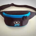 Black fanny pack with a blue zipper and a Rovaniemi roller derby logo